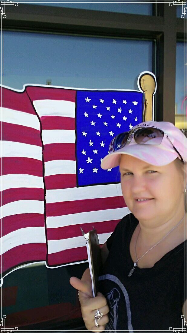 artist M Burgess standing in front of her American flag window painting